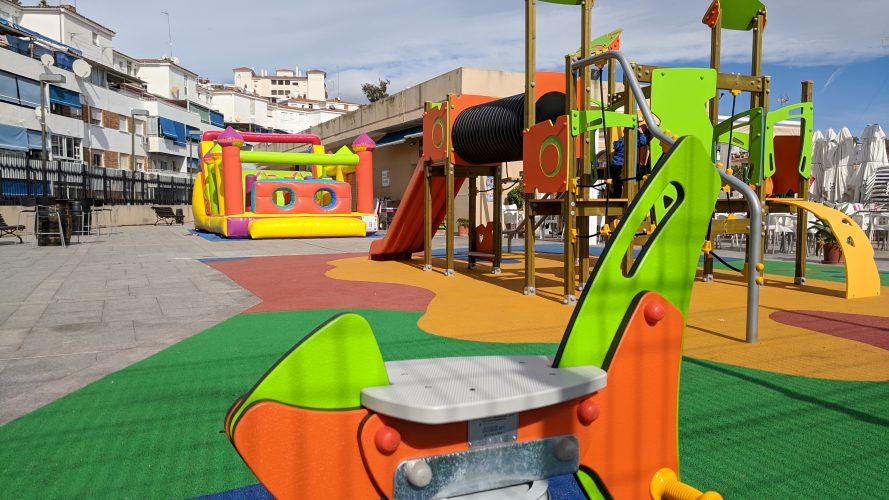 Parque infantil acolchado junto al castillo inflable del bar en Benalmadena
