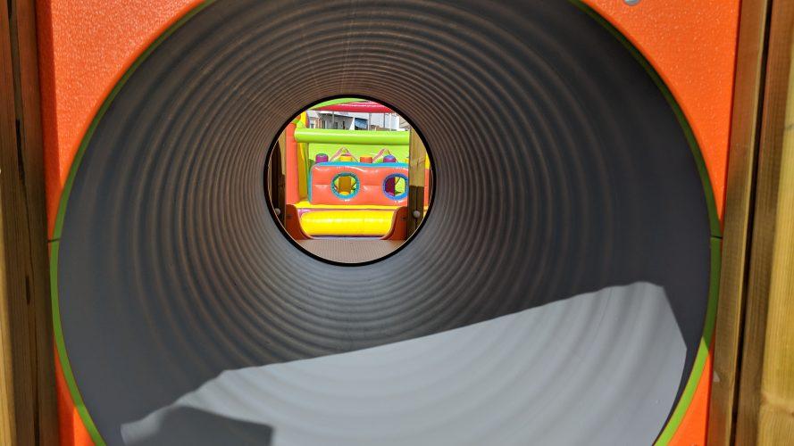 Hinchable al fondo visto desde el tubo del parque infantil