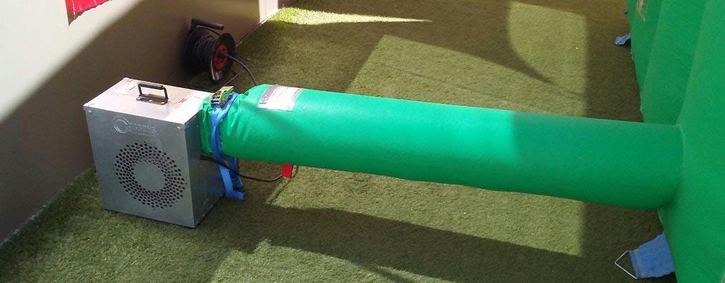 Soplador de aire conectado a la manguera del castillo inflable